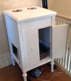 Cat feeding litter box station repurposed from a victrola cabinet. Keeps the doggies from eating the cats food. By Charmaine Benton