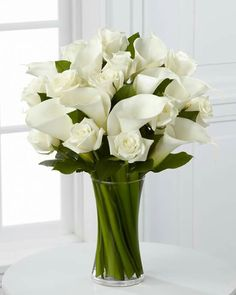 Luxury White Rose and Calla Lily Vase. Beautiful white roses and calla lilies are simply set amongst lush greens in a clear curved glass vase to create a meaningful gift they are sure to love. Modern Flower Arrangements, Vase Arrangements, Funeral Flowers, Wedding Flowers, White Flowers, Beautiful Flowers, Elegant Flowers, Calla Lily Centerpieces, White Rose Centerpieces