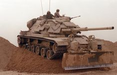 Marines from Company D, 2nd Tank Battalion, drive their M60A1 main battle tank over a sand berm on Hill 231 while rehearsing their role as part of Task Force Breach Alpha during Operation Desert Storm.  The tank is fitted with reactive armor and an M9 bulldozer kit.
