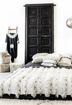 Modern Bohemian: Moroccan bedroom with handira bedspread on low bed, white-washed baskets, black and white palette.