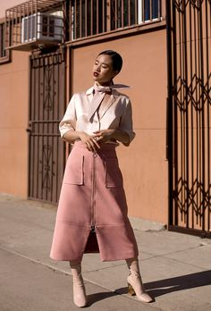 How to wear pastel pink: street style inspiration and outfit ideas from @stylecaster | @nalieli blogger in silk scarf blouse and zip-front midi skirt