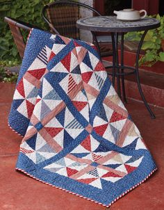 """Everyone loves patriotic quilts, like Summer Picnic by Tricia Lynn Maloney. Pinwheels and Americana colors make this patriotic quilt pattern a great """"blanket"""" for watching fireworks on the 4th of July and an appealing throw-size quilt for your home."""