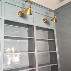 Lacquered Library | Paint Color: Benjamin Moore Water's Edge with stunning brass lights
