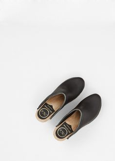 """Handmade, black leather clog wedge with an open back and rounded toe. 3.25"""" heel in beige polished wood with sole in tan treaded rubber. Exposed staple detail at platform. Slips on. The No. 6 Old School Clog tends to run a size small. We recommend sizing up."""
