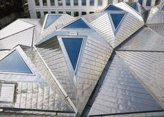 Triangular skylights set into a faceted stainless-steel roof direct daylight into the reading room of this library.