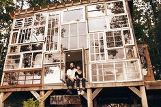 This artist couple built a house out of reclaimed windows. The interior has wood paneled floors, wood paneled walls, rustic decor, simple furniture, and a wall of windows overlooking the landscape.