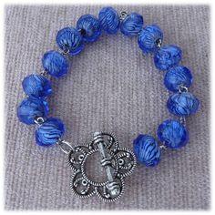 Pulseira em azul marinho conectadas e fecho metálico em formato de flor.  http://artebijuarmanda.blogspot.pt/2012/08/r02.html