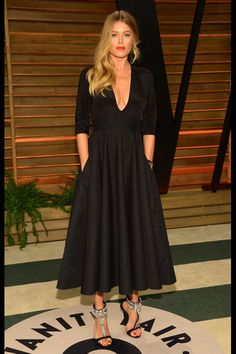 Doutzen Kroes tiene el factor cool: sólo eso puede explicar cómo transformar un sencillo vestido negro de corte midi en un hallazgo estético. Su melena natural, sus labios rojos y esas sandalias joya contribuyeron al fenómeno
