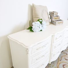 """This lovely dresser is perfect for any shabby cottage style home. It features 9 drawers. This unique piece features ornate fronts decorated with rose appliques! Simply beautiful. Accessories shown are not included.  <br><BR> • Wood/Glass/Metal<BR> • White<BR> • With soft cloth when necessary<BR> • 20.5""""D x 64""""W x 31""""T<BR> • 9 Drawers<BR> • This is a Bella Cottage exclusive one-of-a-kind item"""