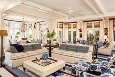 A customdesigned, braided rug ties together a room of blueandwhite accents The ottoman is topped with a tray of cream leather and surrounded by sofas reupholstered in durable white indooroutdoor fabric perfect for a beachside home Great Room Living Eclectic Coastal Transitional by Taylor & Taylor