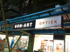 Bon-art optiek heeft haar reclamegevel verdeeld in twee delen. Waaronder (zeer belangrijk) het woord optiek. Dit valt op met behulp van de witte achtergrond. Herkenbaarheid van de winkel is belangrijk. Prima reclame!