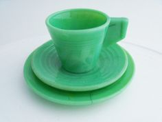 This sweet little 3pc child's tea setting is made of an apple green jadeite slag. The set includes a tea cup, saucer and snack plate. The style is called Chiquita made in the 1940s. The Chiquita line is commonly attributed to Akro Agate, but was actually manufactured by Alley Agate.