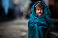 Un bimbo avvolto da una sporca coperta blu passeggia ad Ahmedabad, in  una delle baraccopoli più povere dell'India. Un   monaco birmano dorme nel suo monastero, mentre viene immortalato   fotografo di Finale Emilia  Alessandro Bergamini . Il suo è stato un  viaggio dall'Italia alla sco