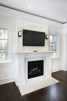 This wooden mantle, with a marble hearth, are a brilliant white color for a modern touch on a fireplace. The TV creates the perfect middle ground for modern and luxurious decor.: via @homestratos