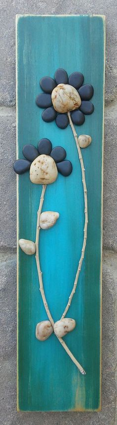 Pebble Art depicting two little flowers on a bright blue green background on reclaimed wood, with pebbles and twig 15 1/2 x 3 1/2
