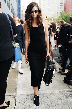 Lily Aldridge wears round sunglasses, a black midi tank dress, and Adidas sneakers