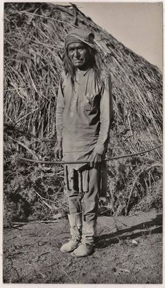 Description:Outdoor portrait of Poleh-Uaha (Poteh-tlaha ?), holding a bow. He wears a long cotton shirt, pants, a kerchief, and hide boots. He stands in front a large brush shelter. Culture/People:White Mountain Apache Date created:October 1919 Native American Photography, Native American Photos, Native American Indians, American Art, Apache Indian, Native Indian, Indigenous Tribes, First Nations, Old Photos