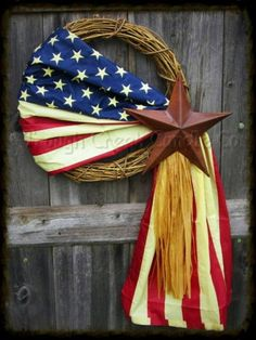 """This Americana wreath is made up of a 18"""" grapevine wreath draped with a replica Americana flag, raffia, and adorned with a rusty tin star."""