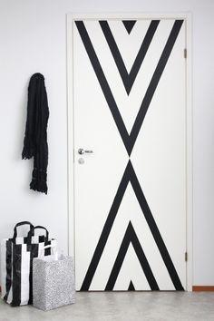 Een saaie witte deur kan op een eenvoudige manier in een grafisch kunstwerk veranderd worden met behulp van zwart tape.
