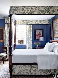 The nanny's room is furnished with an American four-poster; the curtain and canopy fabric is by Brunschwig & Fils, and the walls are covered in a Fromental silk wallpaper.