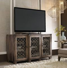 The Entertainment Console 64 inches features three wood-framed doors with decorative overlay and seeded glass or wood panel option and two adjustable shelves behind each door.