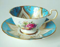 Vintage Paragon cup and saucer set, circa 1930s. Turquoise and heavy gold gilt with multicolor fruit and flowers adorn the bowl of the cup and