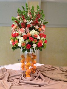 Buffet arrangement of white hydrangea, roses, snaps, peach and orange roses, garden roses, gerbs, snaps, green viburnum and bells. Oranges in the vases.