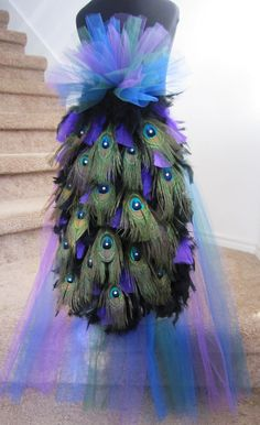 This is a beautiful Peacock Bustle/Tail.This is a very flowy tail with added tulle for extra added color. This can make a wonderful addition to a peacock costume or a burlesque outfit. This can also be used as part of a mardi gras costume.