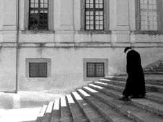 A priest wearing a cassock.  Check out the light on the staircase.  In photography, it's not just about the subject;  it's about the light!