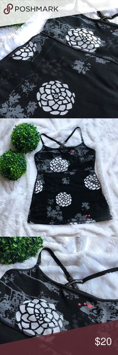 Lululemon Black Crisscross Tank Top With Flowers This is an older style Lululemon black tank top with white flowers. I do not know the name of this style. The inside tag has been removed and this tank top was made before Lululemon started adding the hidden size label. According to the Lululemon website it would be a size 0. It has a 28 inch chest, 18 inches long excluding the straps, and 37 inches around at the hem. Does have a built in shelf bra. The stripes on the straps are coming off but…