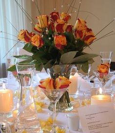 Wedding Flowers A simple arrangement of gorgeous orange roses is transformed into a stylish centrepiece by the pearls threaded on to the grasses. Would like this with white/cream roses