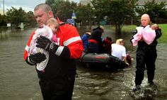 Newport News firemen Corey Archer and Jermiah Johnson carry babies from a boat at City Line apartments after heavy rain caused flooding in the area Saturday. (Rob Ostermaier / August 25, 2012)