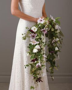 Centuries ago, brides carried open wreaths made of herbs (even garlic!) to ward off evil spirits. Our floral version enlists white lisianthus, purple clematis, and pink nigella flowers woven with pokeweed and exploding grass—and pulls good spirits in.