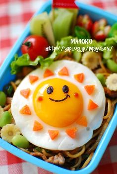 Happy Sun Bento byGMO (site not in english). I's say the sun rays are little carrot pieces, the suns eyes and mouth are cut out from a seaweed sheet, and the rosy cheeks would be little dabs of sweet chilly sauce (or maybe tomato sauce).