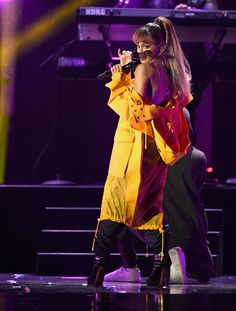 Ariana Grande rocked the 2016 iHeartRadio Music Festival stage wearing an orange trench coat from the #VersusVersace Spring Summer 2017 show. #VersusCelebrities