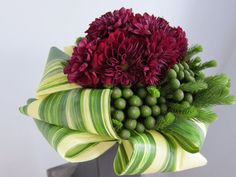 Ribbon-like folds of variegated aspidistra give a cool texture to any bouquet... here, paired with brunia and dahlias.