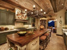 Tuscan design celebrates its simple luxury and at-home feel through this warm kitchen. A low, cove-vaulted brick ceiling, hex terra-cotta flooring and rustic sage cabinetry in this kitchen deliver natural warmth and character.