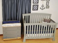 Transportation theme nursery with navy map fabric and yellow trim on a grey crib