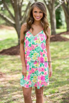 Get away in this vibrant tropical dress. Features a white bodice with neon flowers, a plunging v-neck, and spaghetti straps. Lining underneath for extra coverage. Pair with sandals or wedges for the sweetest look!
