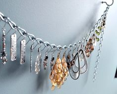 Jewelry display made of simple wall hooks and a chain... brilliant!