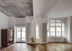 raw concrete ceilings with floors that combine oak parquet with decorative tiles