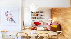 In+the+living+room,+a+rose-colored+velvet+sofa+serves+as+a+whimsical+statement+piece.+Thonet+style+bentwood+chairs+surround+an+oval+dining+room+table+under+a+modern,+white+pendant+light.