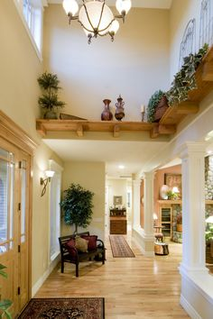 The high ceiling in the very beginning of the entryway soars up to a high window. Shelving lines the area. The mostly open-concept room has been differentiated from the living room by a short section of wall and columns.