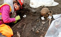 An archaeologist works near skeletons found in the Bedlam burial ground on the future site of a Crossrail ticket hall next to Liverpool Street Station in London March 6, 2015. Archaeologists have started excavating around 3,000 skeletons from the Bedlam burial ground which dates back to 1569 and was London's first municipal burial ground.