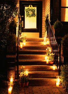 Lining the steps up to your front door with lanterns and a little bit of greenery creates a stunning holiday display, even though it requires minimal effort.   - ELLEDecor.com