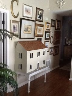 Traditional dollhouse painted same as wall color, on piano bench, part of gallery wall