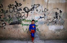 politics-war:    A Palestinian boy dressed in a Superman costume and holding a toy gun in an alley of the Jalazoun refugee camp in Ramallah, West Bank.  Photograph: Muhammed Muheisen