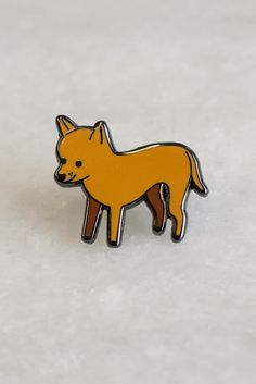 This little dude just wants to hang out on your jacket, and possibly also eat Taco Bell. Designed by Julia Bereciartu. 20mm wide lapel pin in mirrored black metal with hard enamel fill.