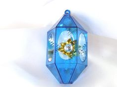 Gold foil flower has a silver center ball and is backed with white plastic holly and evergreen fronds in this blue plastic Christmas ornament