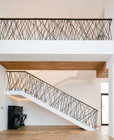 This home features custom railings on the stairs and the top floor, made from randomly placed steel supports that have been powder coated black.